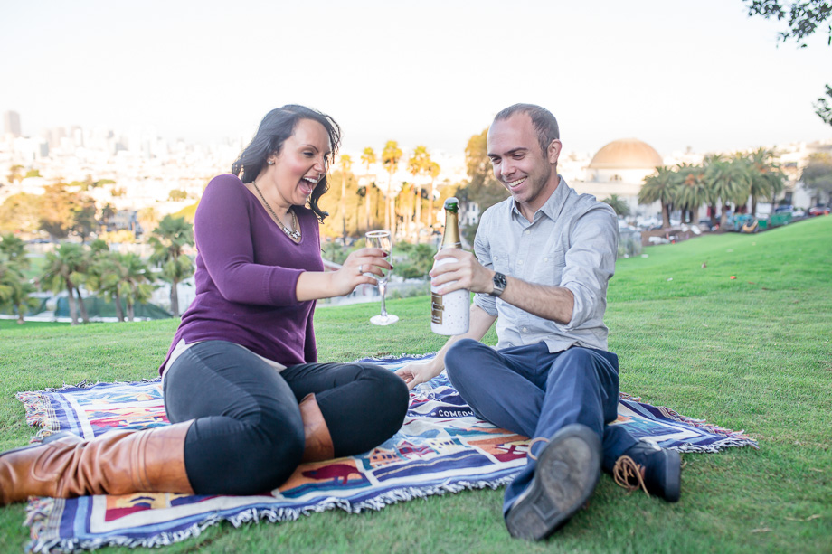 popping open champagne during engagement photo shoot