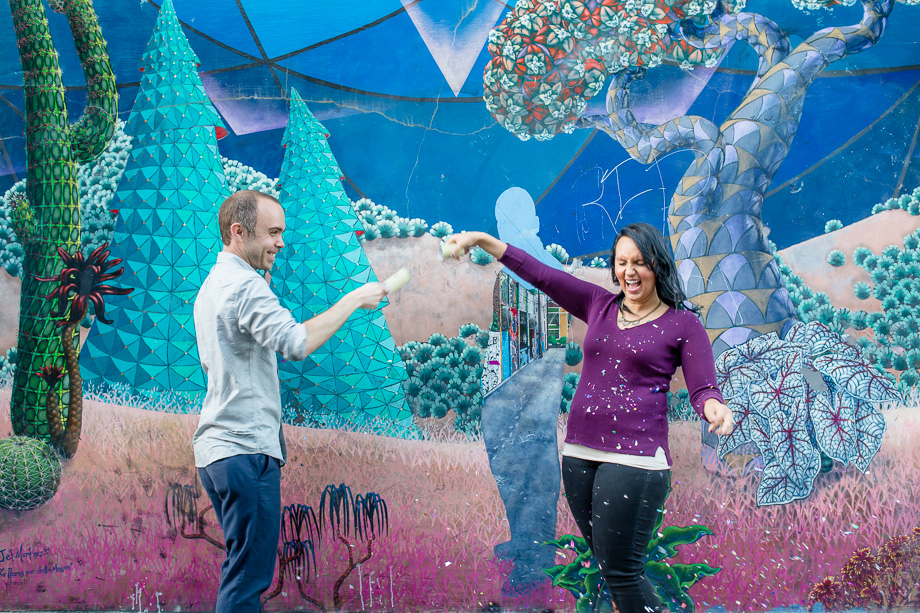 fun confetti fight engagement photo in front of san francisco colorful mural
