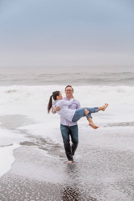 boyfriend carrying girlfriend on the beach in the waves