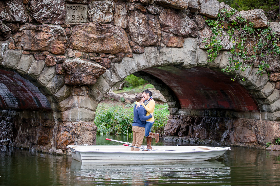 romantic kissing photo on a boat under Stow Lake stone arch bridge
