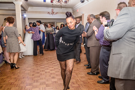 wedding guest in black dress dancing