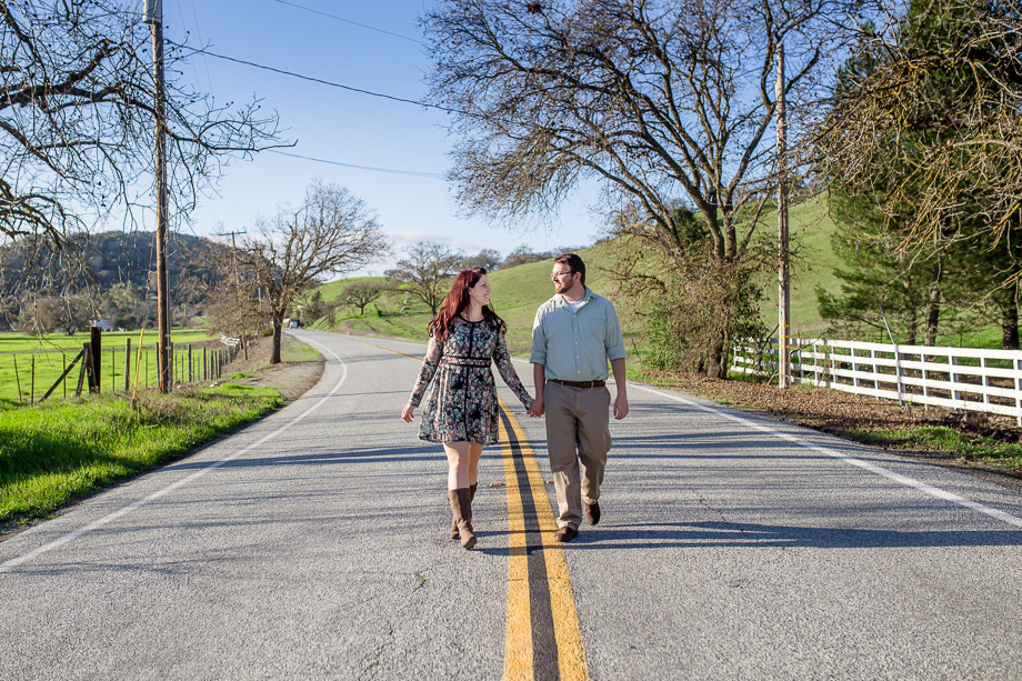 couple holding hands walking along a country highway