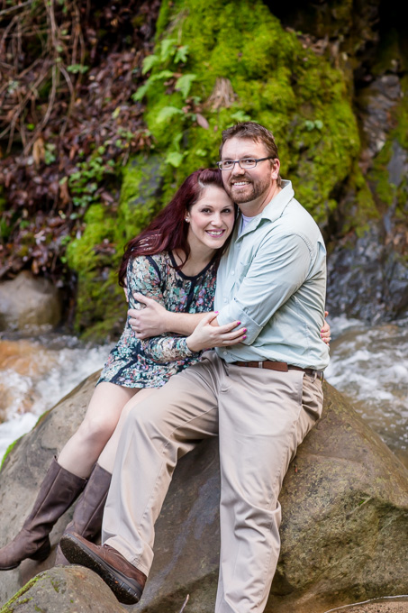 engagement photo sitting on a rock in a river