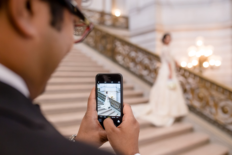 groom taking a cute photo of bride on their wedding day at San Francisco City Hall