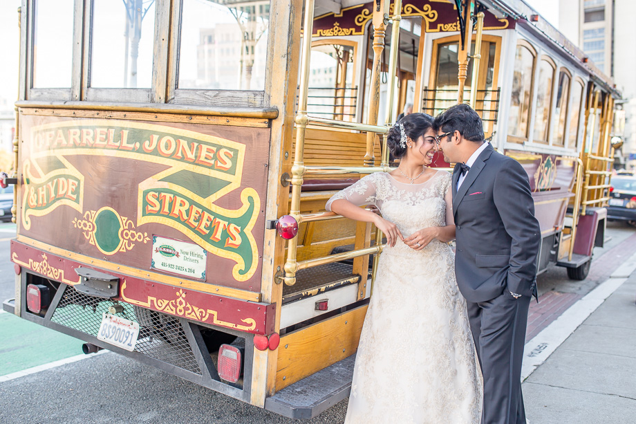 newlyweds with a cable car parked right outside of San Francisco City Hall