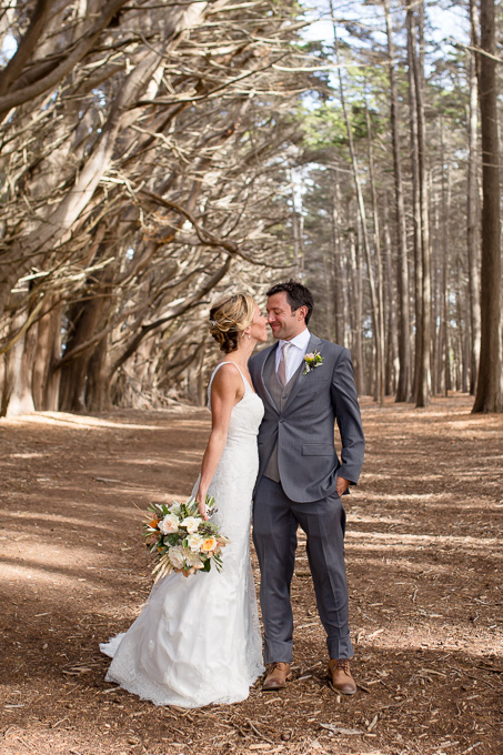 bride and groom kissing under cypress tree arch