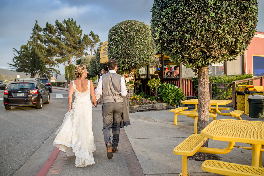 candid photo of bride and groom walking to the jetty from the reception venue