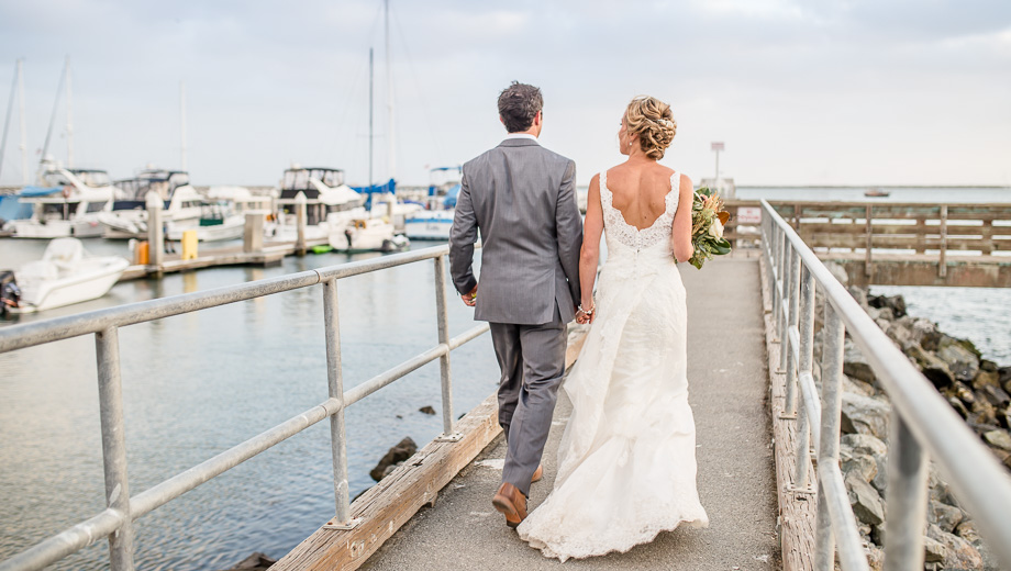 candid photo of bride and groom walking on the jetty - Mavericks Event Center wedding