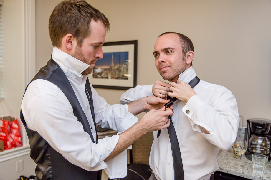 best man tying the tie for the groom