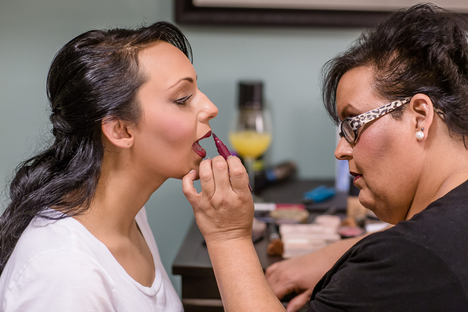 mother putting on lipstick for daughter
