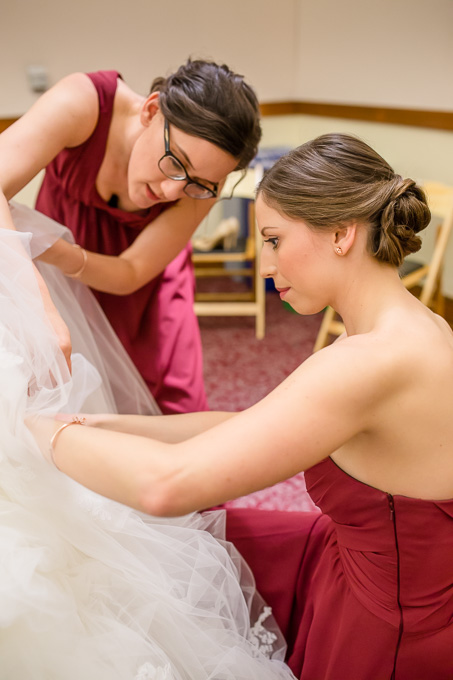 bridesmaids helping with bustling the dress