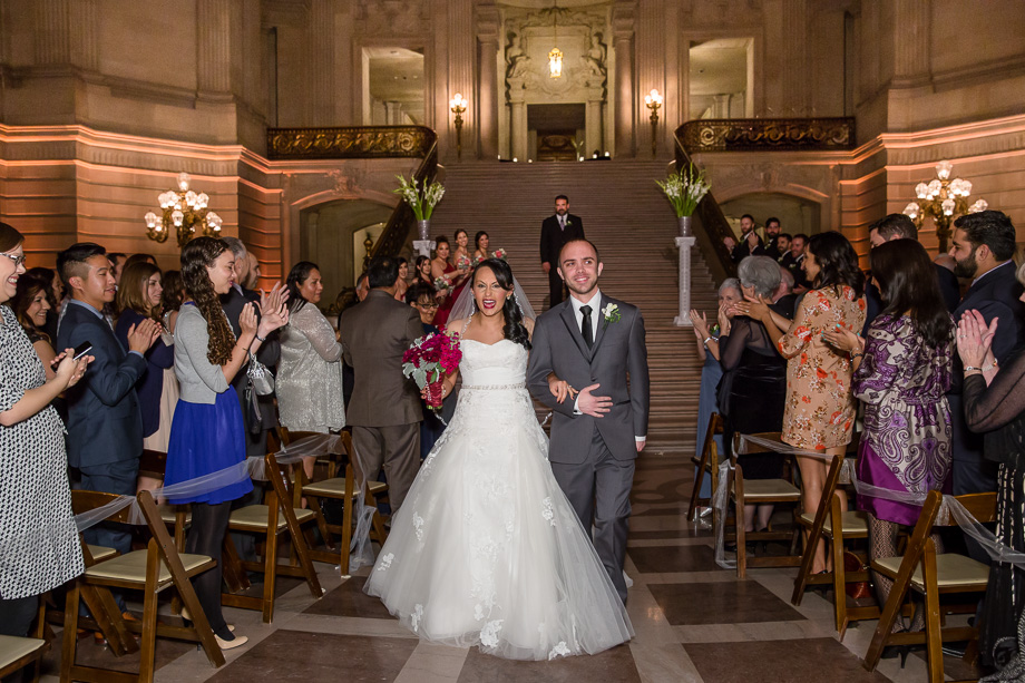 bride and groom walking down the aisle as husband and wife - sf city hall wedding