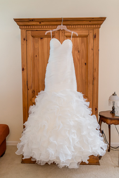beautiful white wedding dress hanging on a dresser