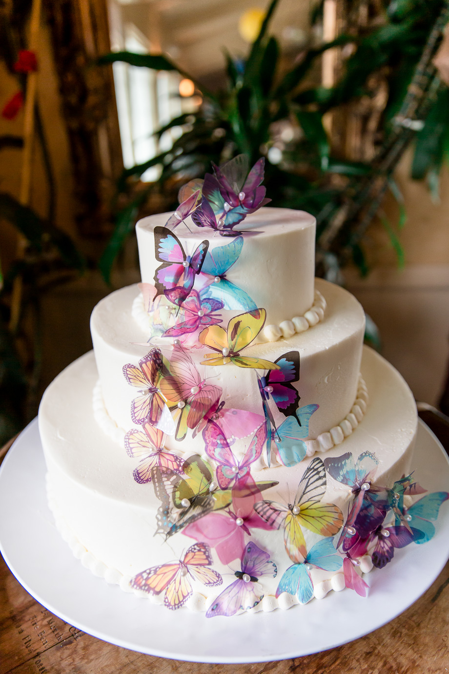 whimsical wedding cake with layers of butterflies