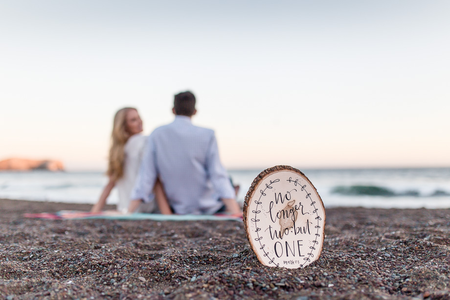 sunset engagement photo with a wooden sign that says no longer two but one