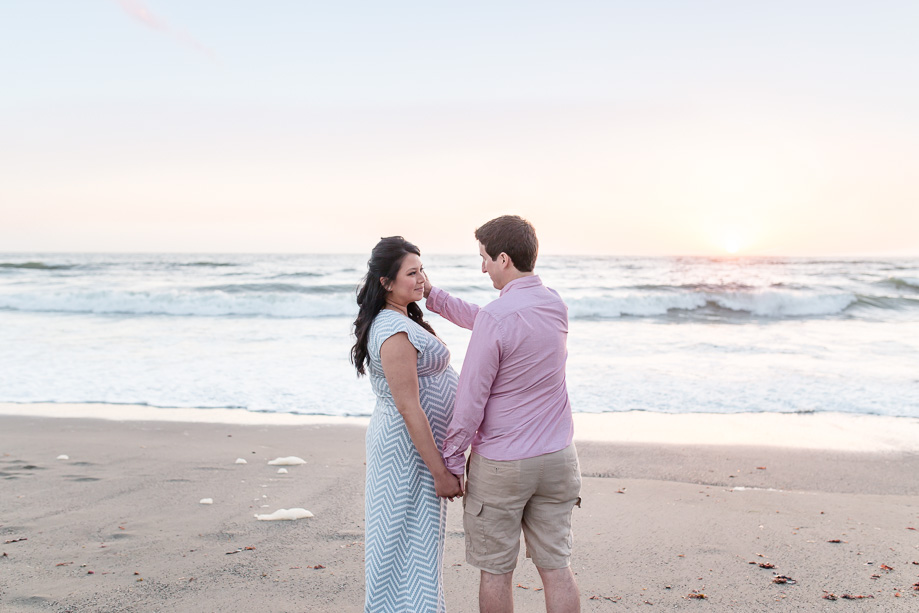 sweet candid moment perfectly captured by the photographer during a beach maternity photo session