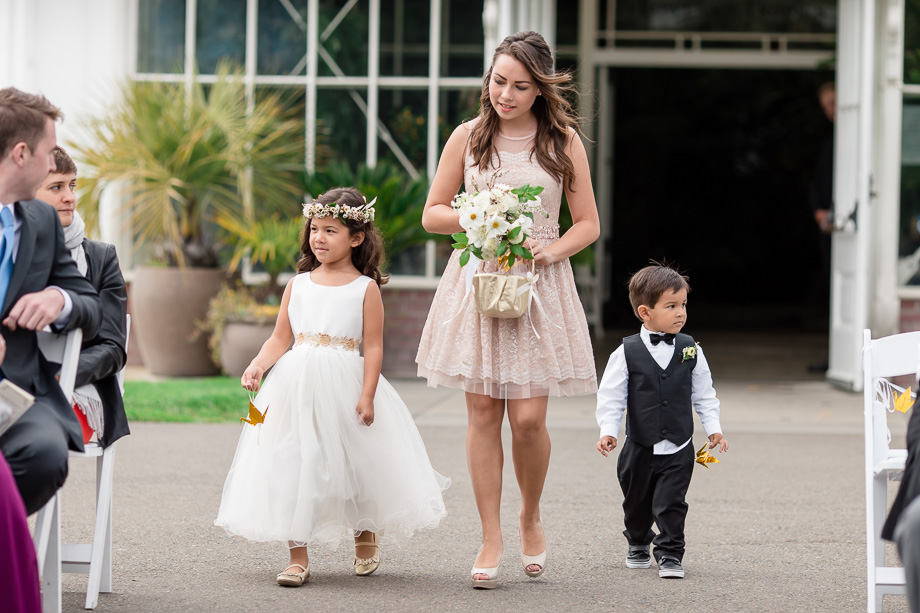 ring bearer and flower girl handing out golden origami cranes instead of flower petals