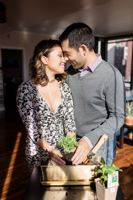 couple have their engagement photos taken at their San Francisco downtown apartment planting together