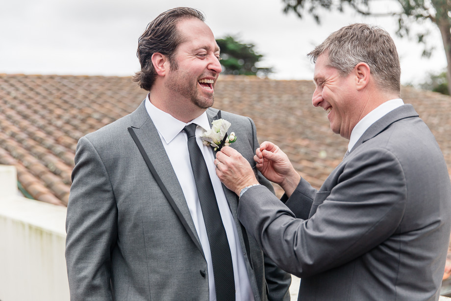 best man pinning boutonniere for the groom