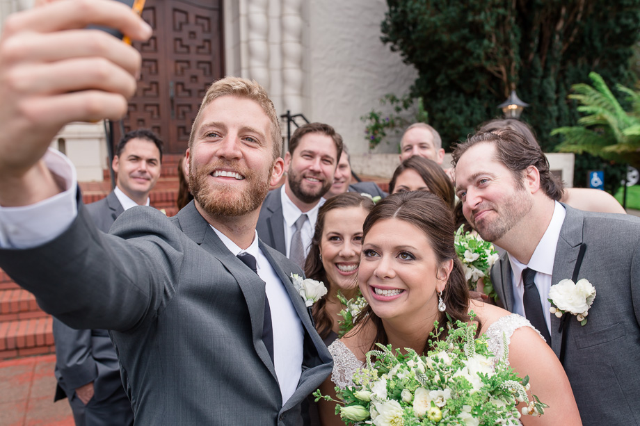 entire bridal party taking a selfie outside the church