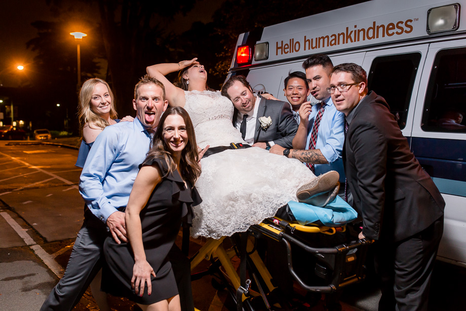 funny photo of the bride fainting on a gurney in front of an ambulance