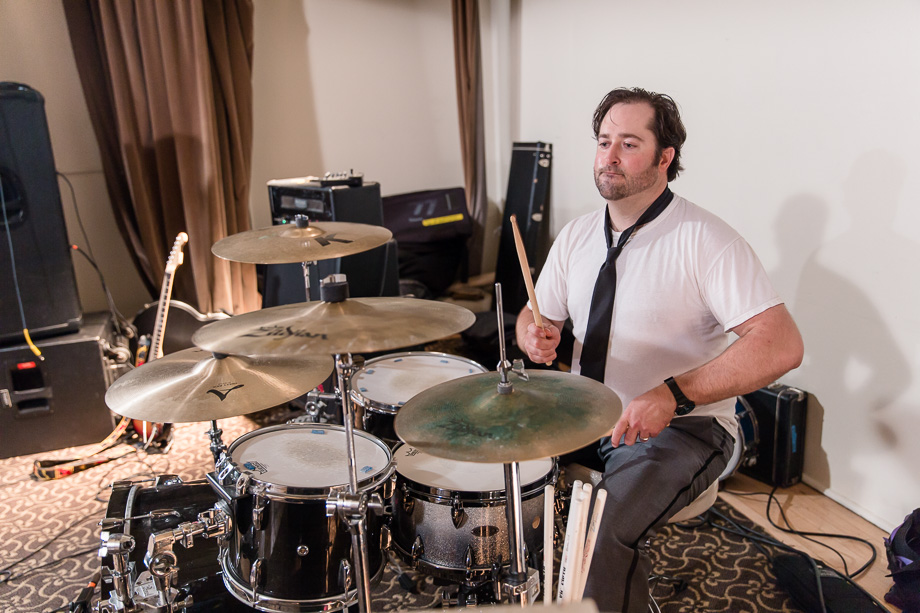 groom plays the drum at his wedding reception