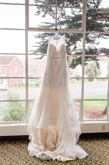 A-line lace wedding gown hanging on the window