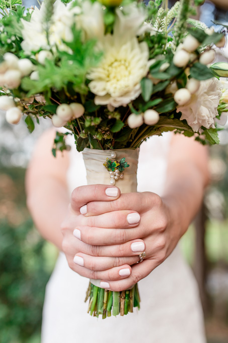 beautiful white and green bridal bouquet with a gorgeous pin