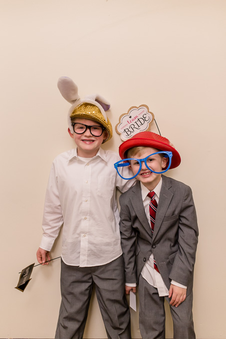 little wedding guests with fun photo booth props