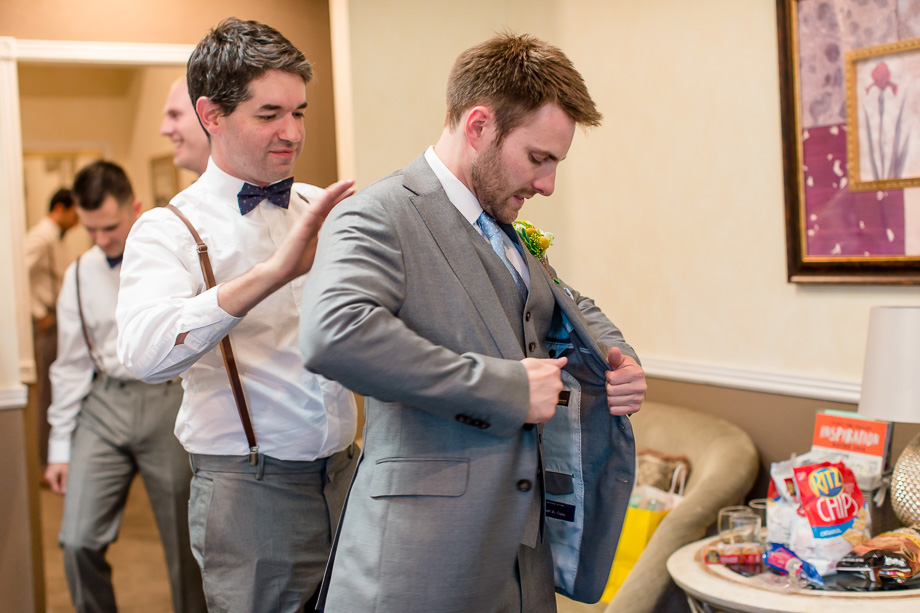 groom getting into his suit by the help of a groomsman