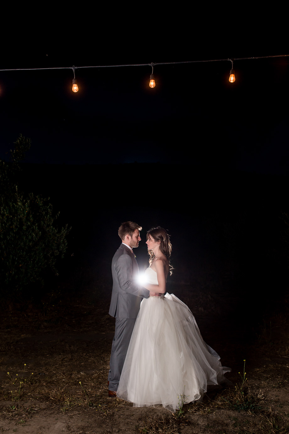 a night shot of bride and groom under the cafe string lights