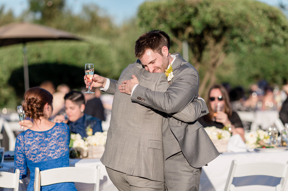 groom hugging his brother best man after the toast