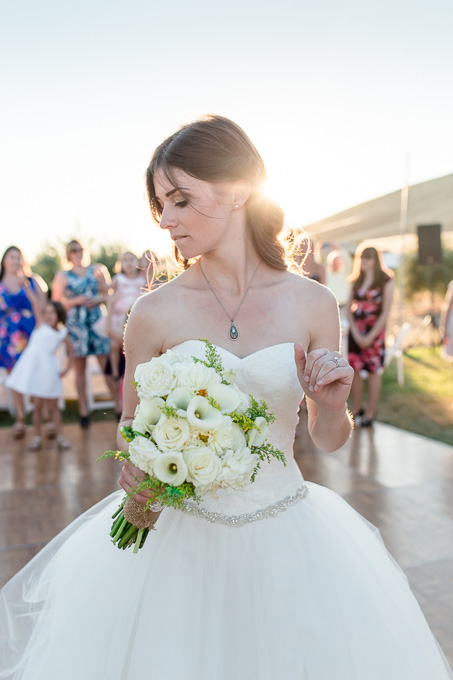 bride tossing the bouquet during sunset