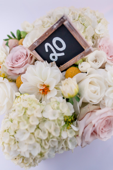 pink and white floral centerpiece with a rustic chalkboard table number - california outdoor wedding