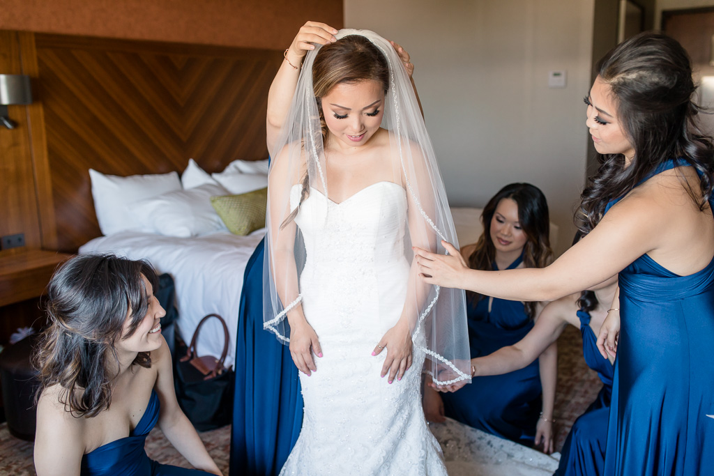 bridesmaids helping bride with her veil and dress