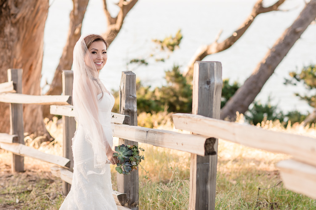bridal photo next to a rustic fence at Coyote Point Marina
