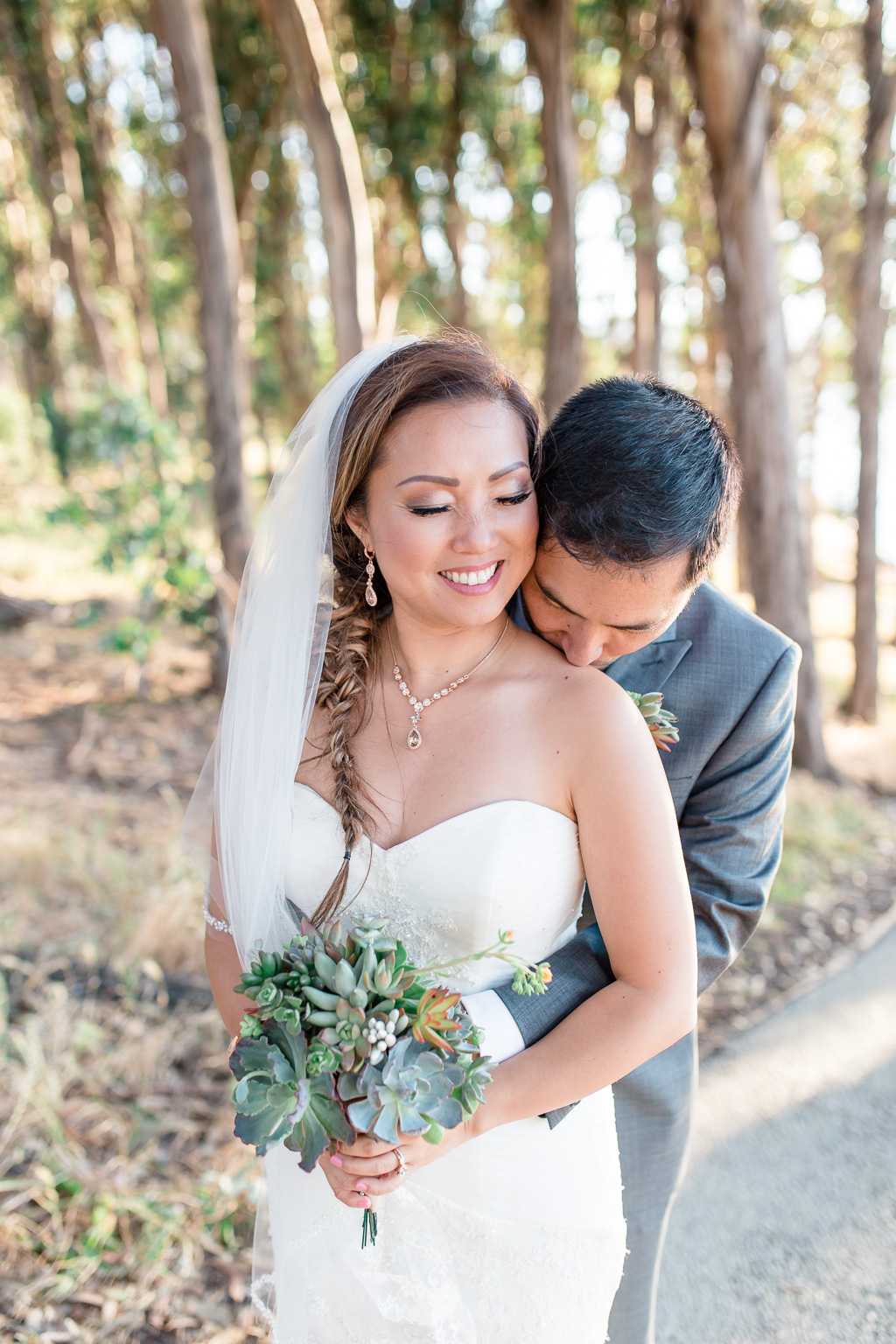 photo of groom and bride holding floral DIY bouquet in the woods