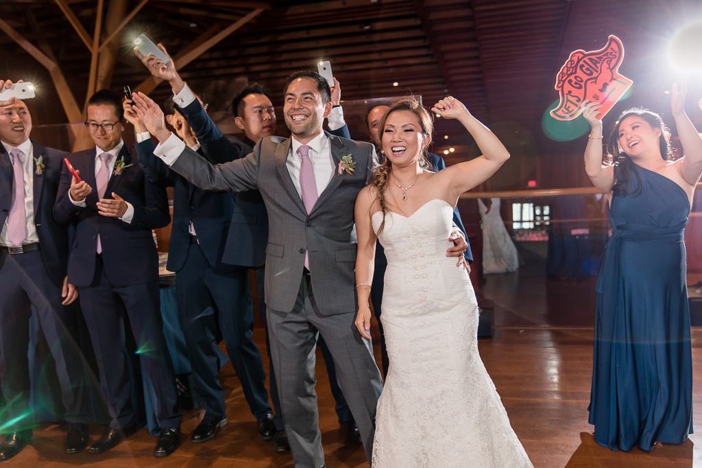 bride and groom dancing welcomed by bridal party waving cell phone flashlights