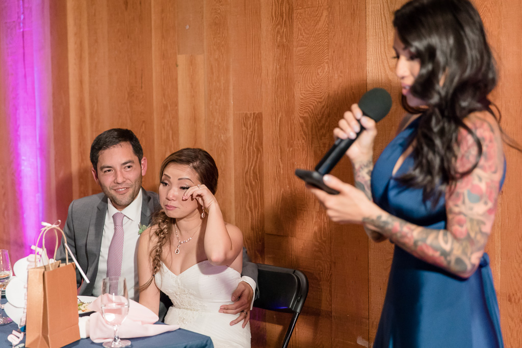 bride wiping away a tear as her sister gives a touching speech