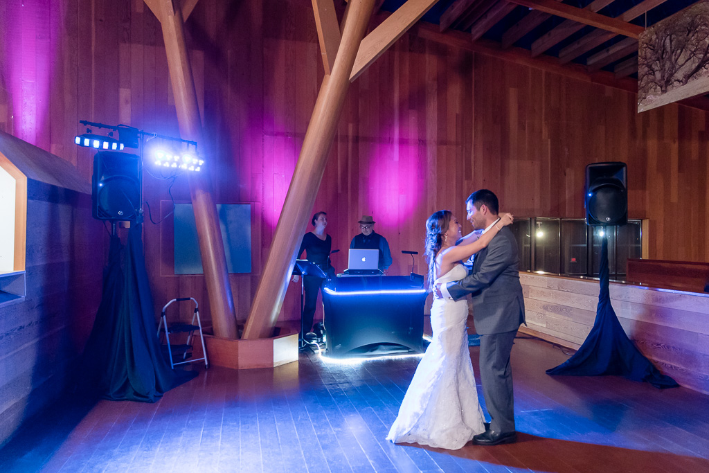 colorful DJ lights shining on newlyweds first dance