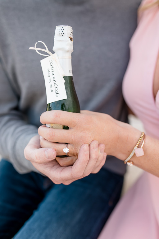 champagne bottle and engagement ring