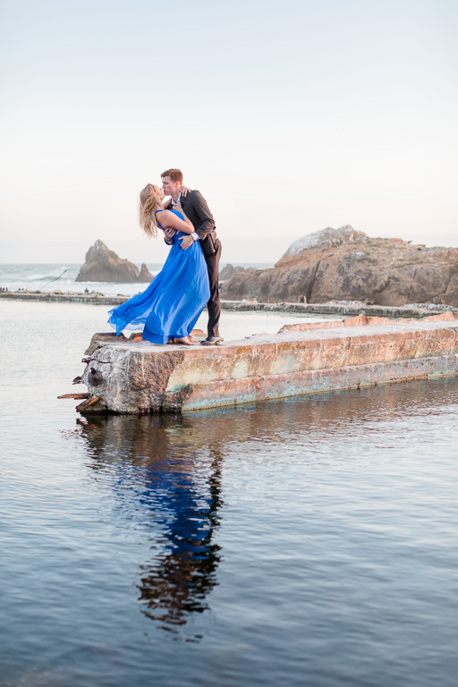 Sutro Baths reflection engagement photo of couple dipping and kissing