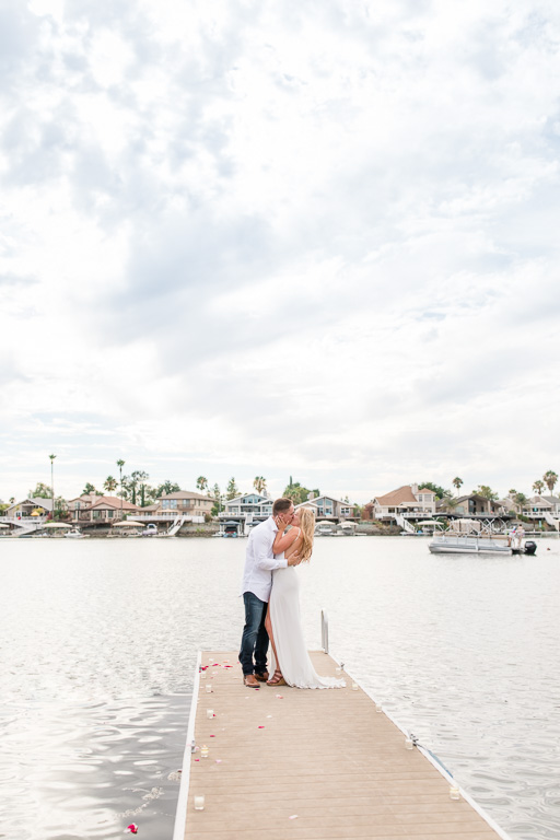 engagement photo at end of dock on a beautiful lake under the sun