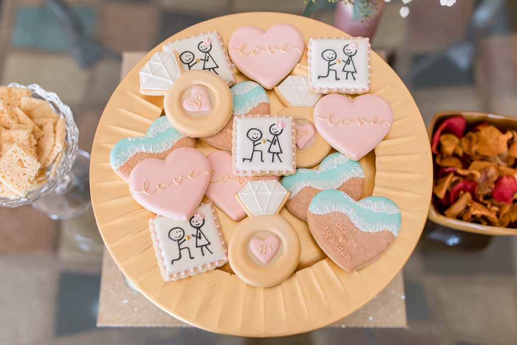 engagement party cookies with super cute drawings of a stick figure proposing