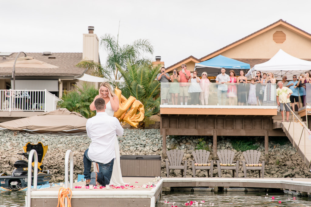 epic proposal reaction on lake dock decorated with candles and flower petals