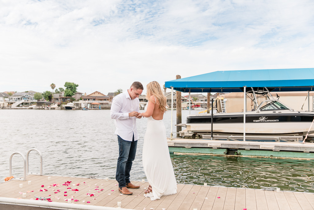 groom-to-be putting engagement ring on his future bride after she said yes