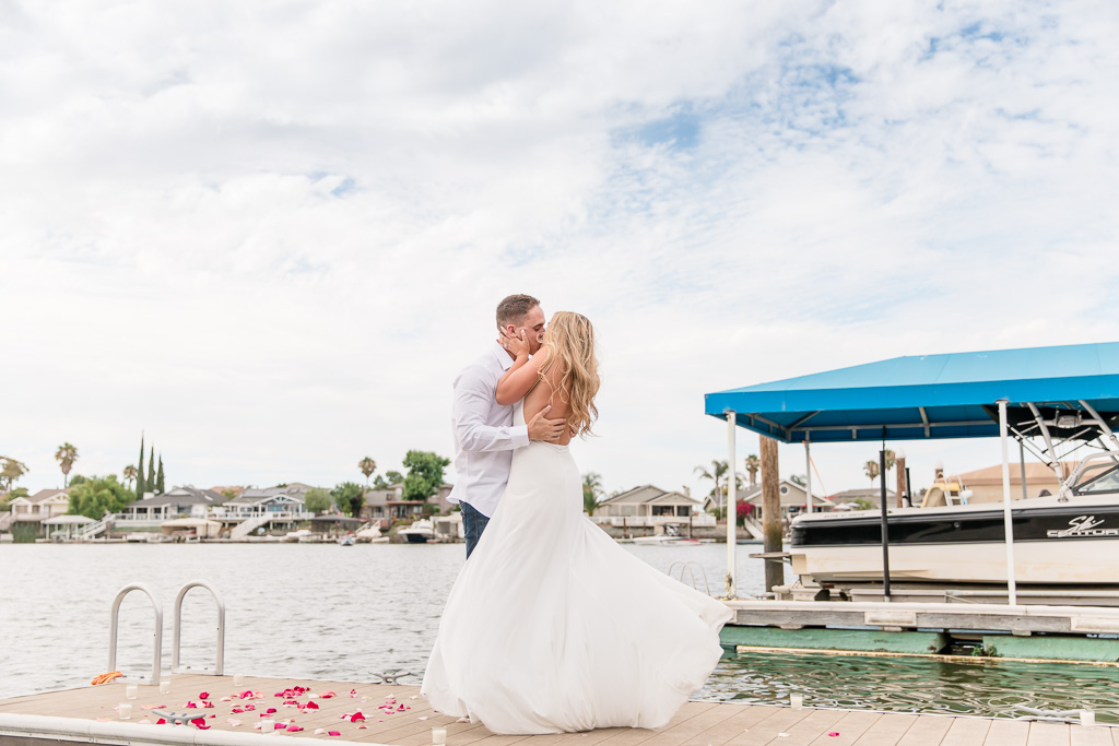 couple kissing on a boat dock with rose petals on the ground