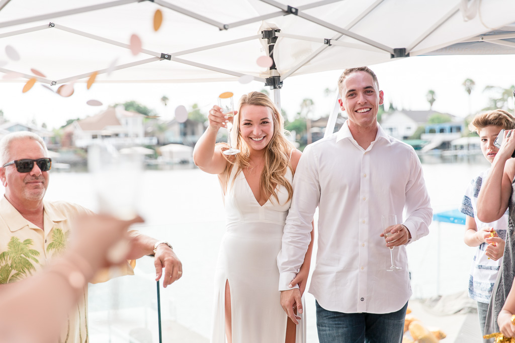 couple raising a glass of champagne at engagement party