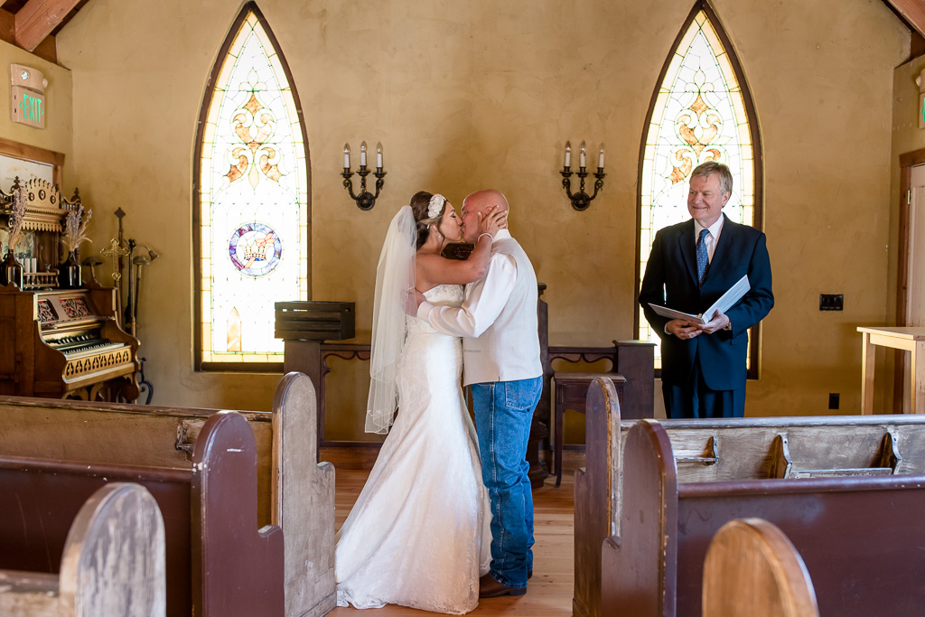 first kiss as husband and wife witnessed by the officiant and photographer