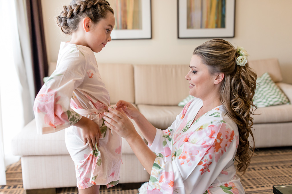 bride helping the flower girl with her floral robe